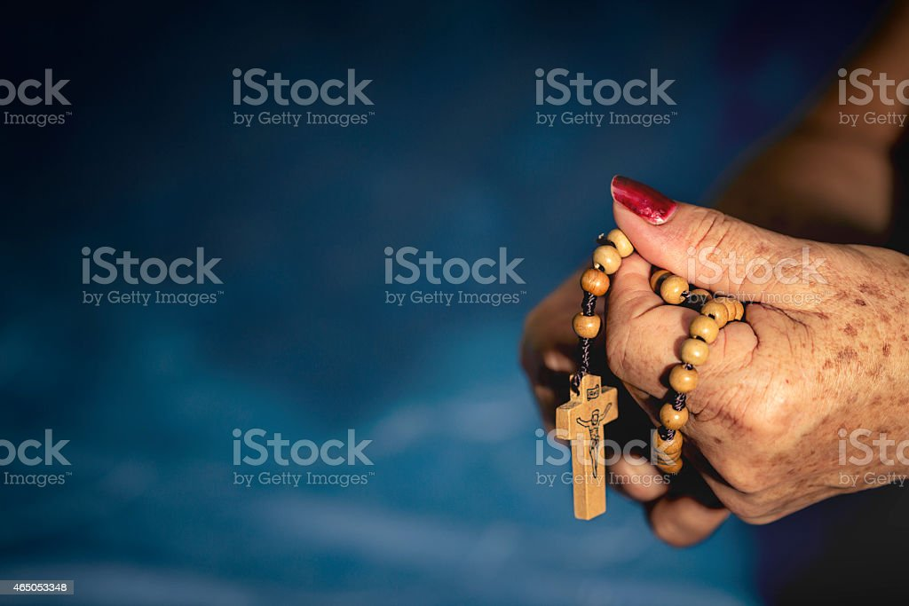 Rosary wrapped in elderly hands. stock photo