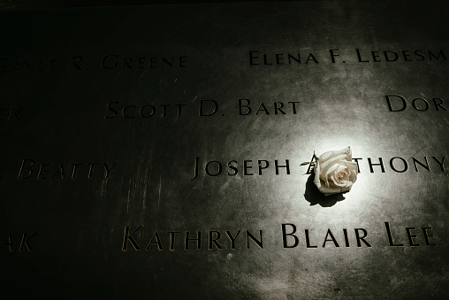 New York City, USA - July 6, 2016: A rose is left at the National September 11 Memorial at Ground Zero in Lower Manhattan. The names of the victims of that day are inscribed.