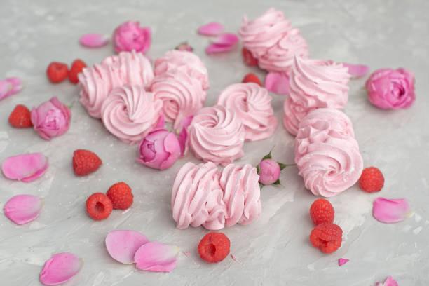 rosen-und rosenblätter, himbeeren, hausgemachte rosa marshmallows auf einem betongrund. - brautparty kuchen stock-fotos und bilder