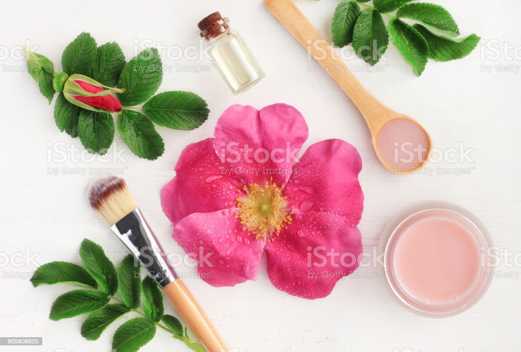 Rose aroma cosmetic products for natural beauty treatment. Fresh pink flower, green leaves, essential oils, skincare mask stock photo