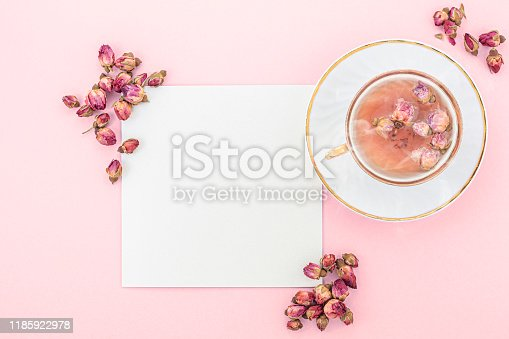 Overhead studio image of an elegant  steaming tea cup with made of Chinese dried roses. The background is pale pink. There is a blank card by the cup, and it is framed by dried rose buds.   (The image coloring is based on PANTONE Blossom color nuances)