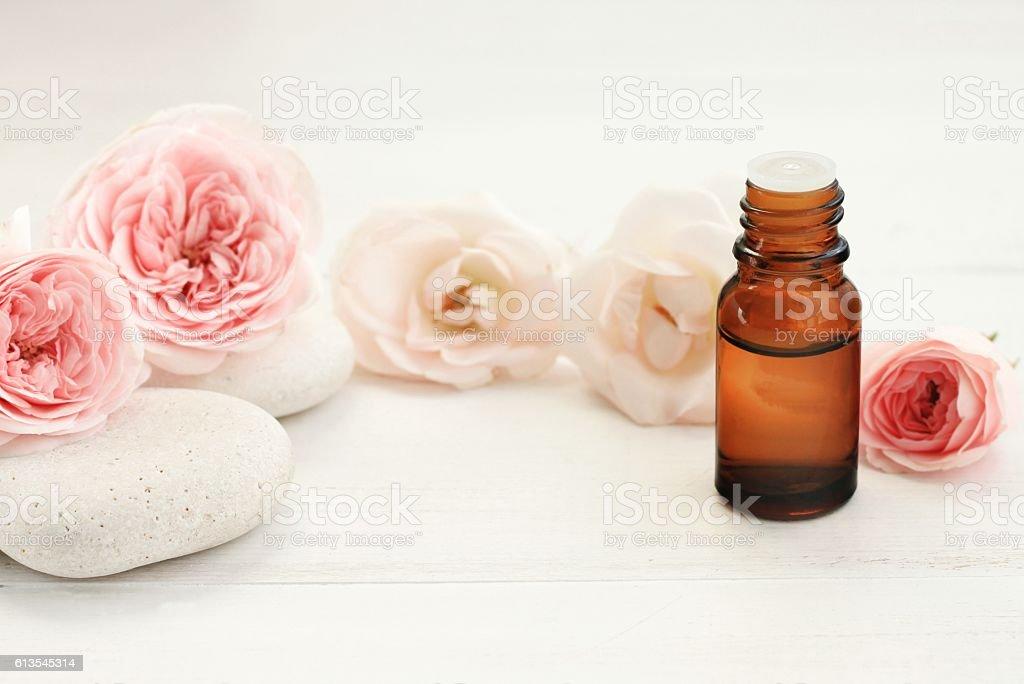 Rose essential oil, flowers, spa stones. stock photo