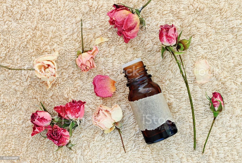 rose essential oil on towel stock photo