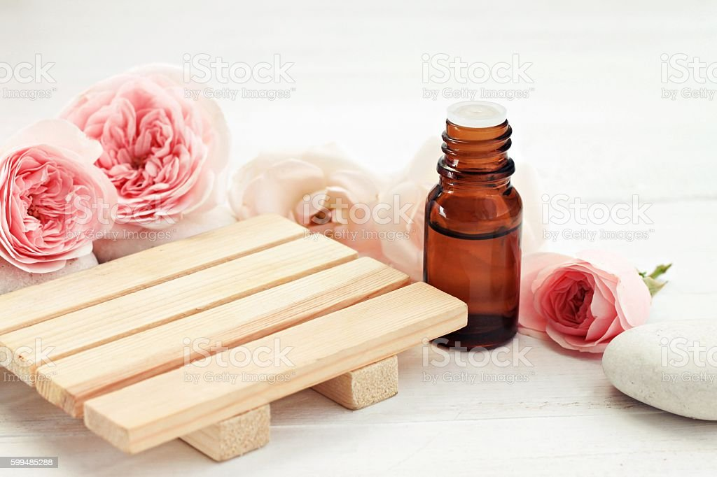 Rose essential oil, wooden surface for product display stock photo