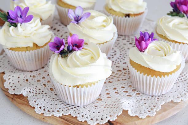 rosenblüte frostende vanille cupcakes mit lila essbaren blumen - hausgemachte hochzeitstorten stock-fotos und bilder