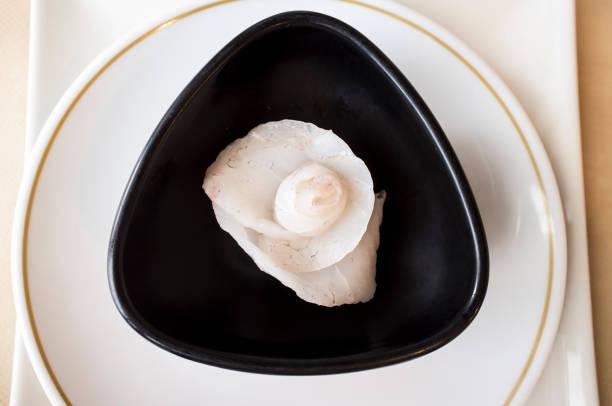 Rose flower shaped cod Sashimi Sushi over black bowl stock photo