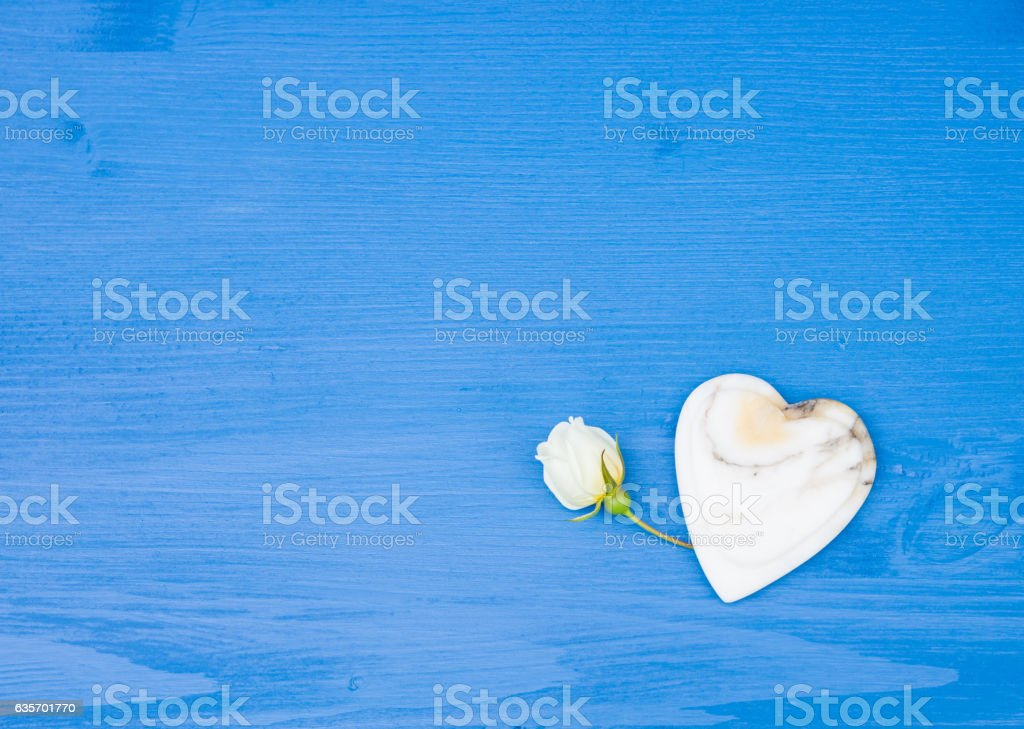 Rose flower with Heart of marble on blue wooden table royalty-free stock photo