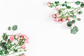 istock Rose flowers and eucalyptus branches. Flat lay, top view 914839340