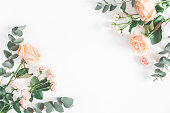 istock Rose flowers and eucalyptus branches. Flat lay, top view 951847770