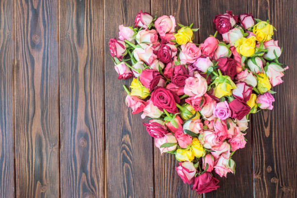 Rose flowers heart on a wooden background. stock photo