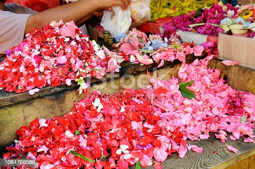 Person preparing flowers petals for culinary purpose. Pink and red rose at marketplace stall display in Asia.