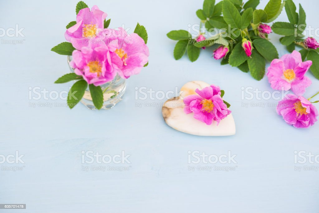 Rose flowers with Heart of marble on blue wooden table royalty-free stock photo