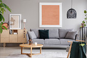 Rose gold painting and poster in bright loft interior with grey sofa near cabinet and wooden table. Real photo