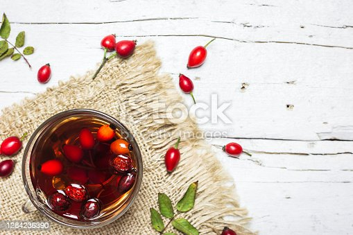 Close-up photo of cup of tea with rose hips on rustic wooden background, top view. Autumn vitamin drink.