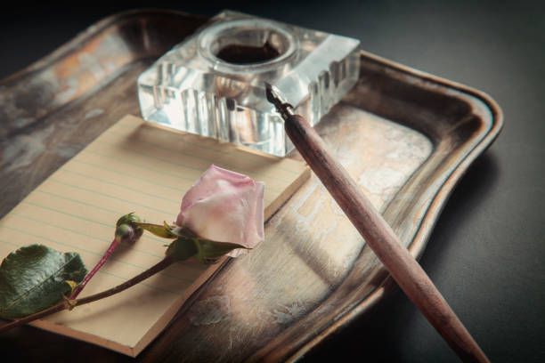 Rose, ink, pen, blank card on a tray on a background of chalkboard. Dark photo . Greeting card, Vintage style sentimentality stock pictures, royalty-free photos & images