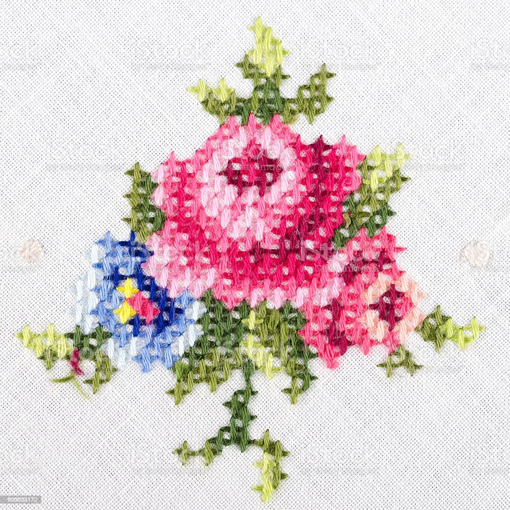 Rose motiv hand embroidery on white linen tablecloth stock photo