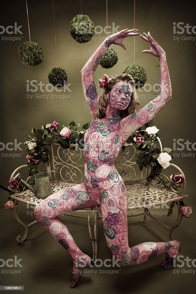 Rose Painted Dancer on Floral Bench stock photo