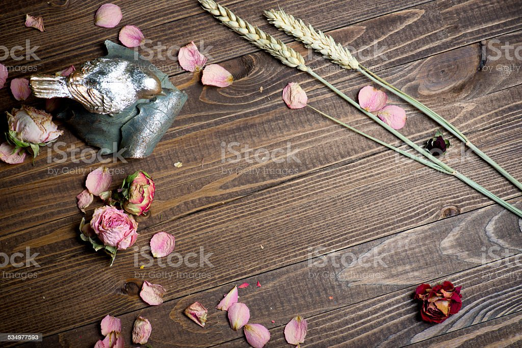 rose petals and dried flowers on old wooden plates. stock photo