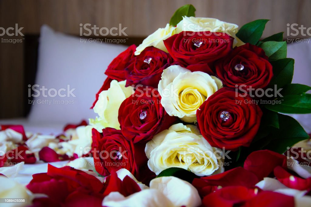 Rose Petals and Roses Bouquet Arrangement on a Bed stock photo