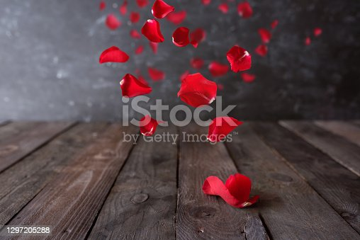 Red rose petals float on dark wooden vintage background. Romantic concept with short depth of field for love, valentines day and wedding. Space for text.