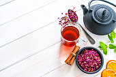 Herbal tea. High angle view of a rose petals tea cup, black teapot and a bowl filled with dried rose petals shot on white table. Dried orange slices, cinnamon sticks and a mint twig complete the composition. The composition is at the right of an horizontal frame leaving useful copy space for text and/or logo at the left. Predominant colors are white and red. High resolution 42Mp studio digital capture taken with SONY A7rII and Zeiss Batis 40mm F2.0 CF lens