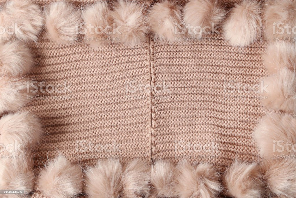 Rose pink winter textile background with copy space and a frame with fluffy tassels stock photo