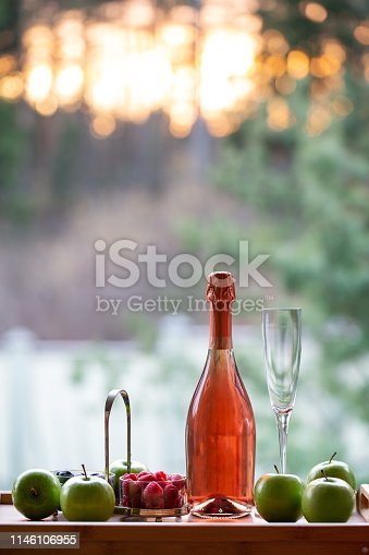 Rose sparking wine with berries and apples on sunset
