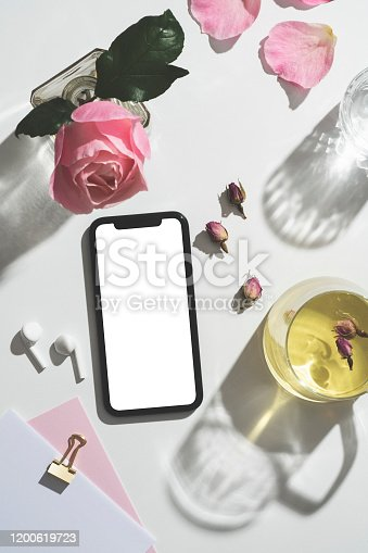 Rose tea and blank screen mobile phone with clipping path table top shot with pink roses