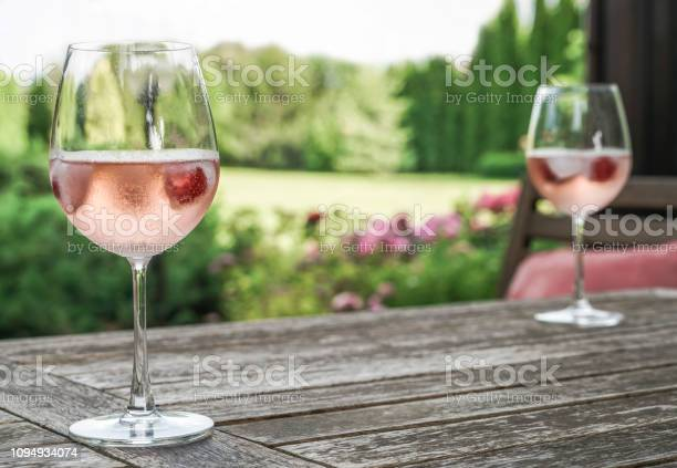 Rose wine glasses on a wooden table at garden picture id1094934074?b=1&k=6&m=1094934074&s=612x612&h=07kbf4nnomzaxmhdyl ygdslom8ehqqbldzhdkkyhwg=