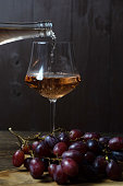 Rose wine is poured into a glass goblet from a bottle. In the foreground, a bunch of grapes is out of focus. The dark key. Vertical orientation.