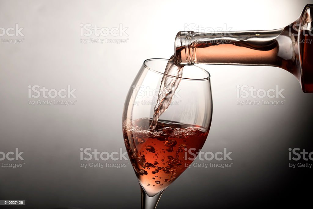 Rose wine pouring into wine glass stock photo