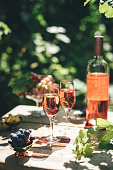 Rose wine tasting, glass of rose wine poured from bottle outdoors in garden party in vineyard, ripe grapes on wooden table, sunlight, harvest time, copy space