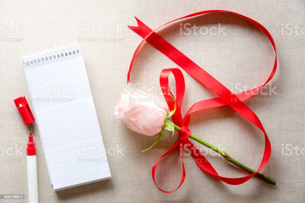 Rose with ribbon in shape of 8 and a notebook stock photo