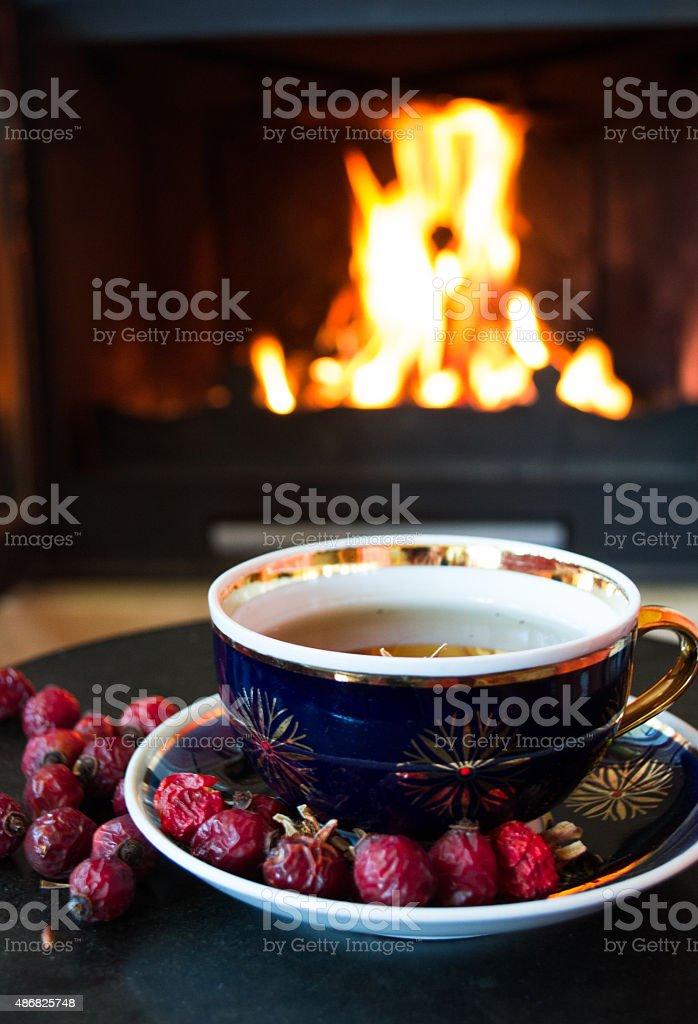 Rosehip tea near fire place stock photo
