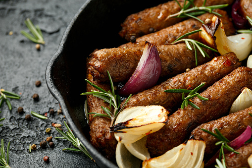 Rosemary and onion vegetarian vegan sausages oven baked in cast iron skillet frying pan.