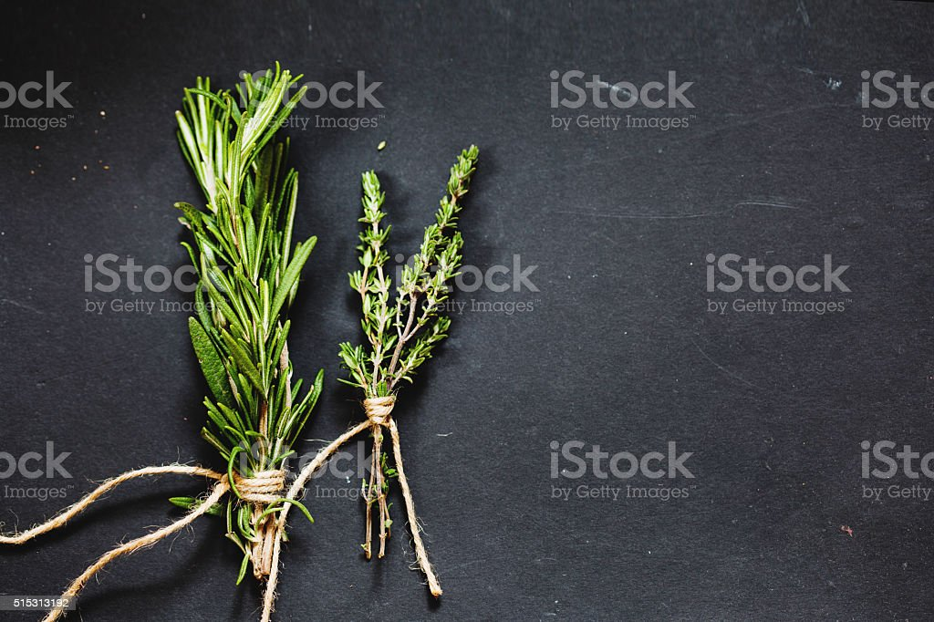 Rosemary and thyme bounds on a dark grey board stock photo