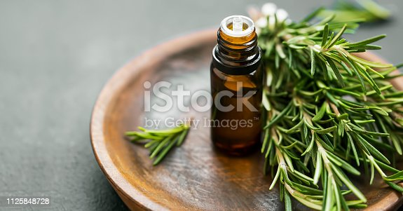 istock Rosemary essential oil bottle with rosemary herb bunch on wooden plate, aromatherapy herbal oil 1125848728