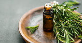 Rosemary essential oil bottle with rosemary herb bunch on wooden plate, aromatherapy herbal oil