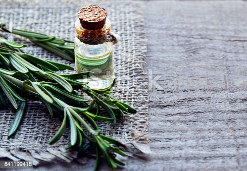 istock Rosemary essential oil in a glass bottle with fresh green rosemary herb on old wooden table.Rosemary oil for spa,aromatherapy and bodycare.Extract oil of rosemary. 841199418