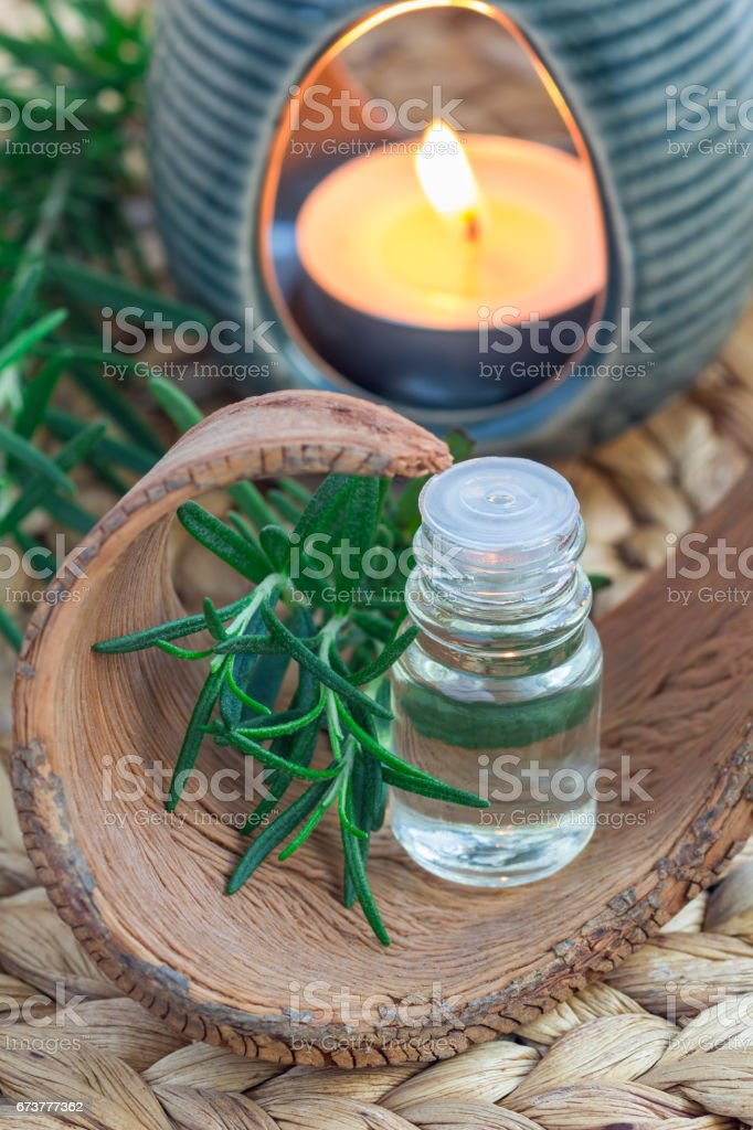 Rosemary essential oil in glass on woven mat with spa background, vertical photo libre de droits