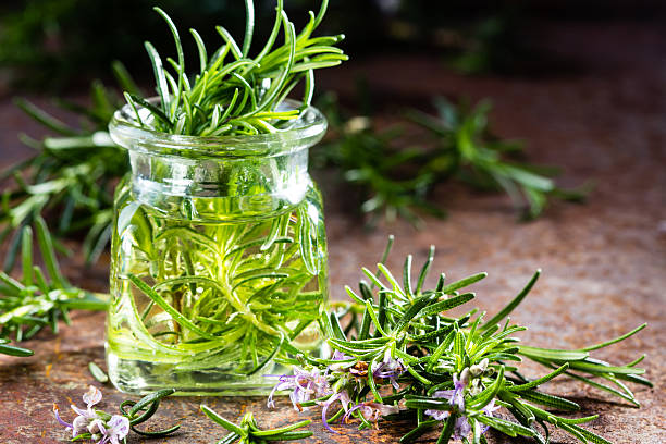 rosemary essential oil jar and plant with flowers, rustic background - oli, aromi e spezie foto e immagini stock