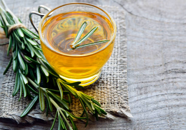 Rosemary herbal tea in a glass cup on rustic wooden background. stock photo