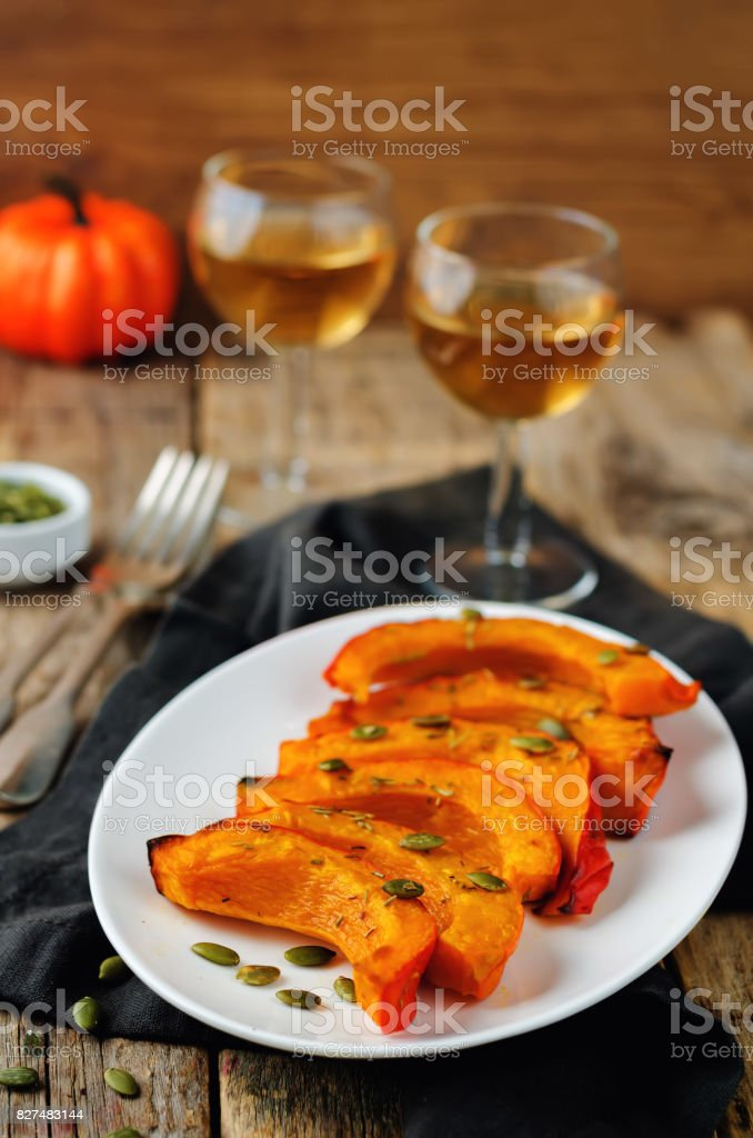 Rosemary honey roasted pumpkin wedges with pumpkin seeds stock photo