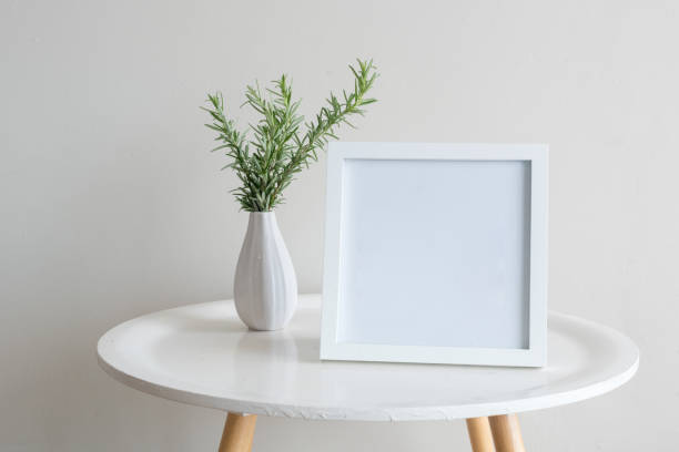 Rosemary in small vase with blank frame on table against wall stock photo