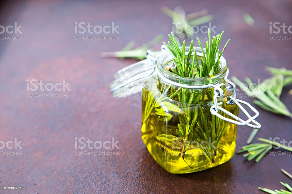 Rosemary oil. Rosemary essential oil jar glass bottle and branch stock photo
