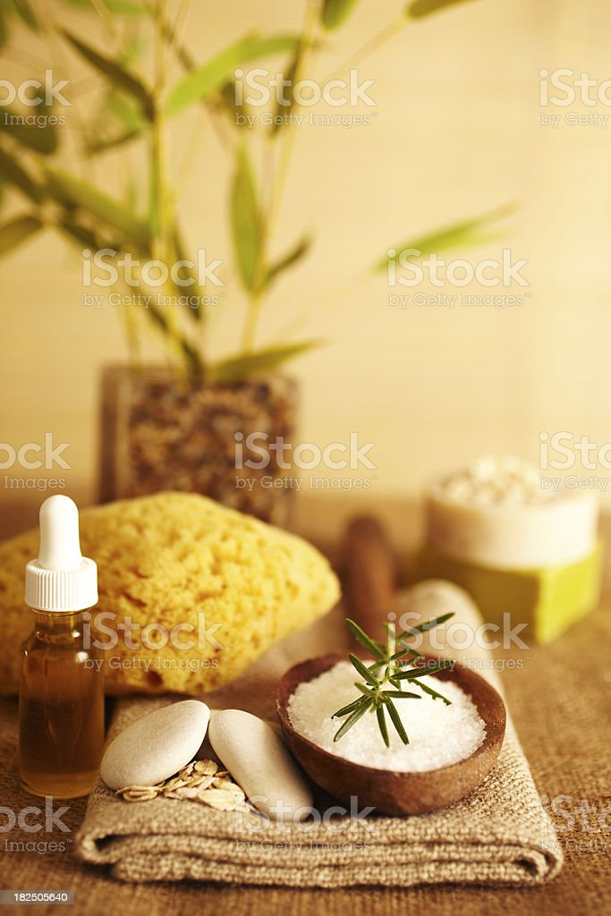 Rosemary on bath salt scrub in wooden spoon and oil royalty-free stock photo