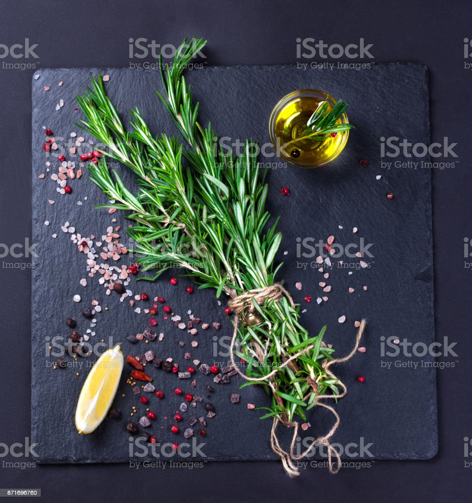 Rosemary plant, salt and spices on black slate board stock photo