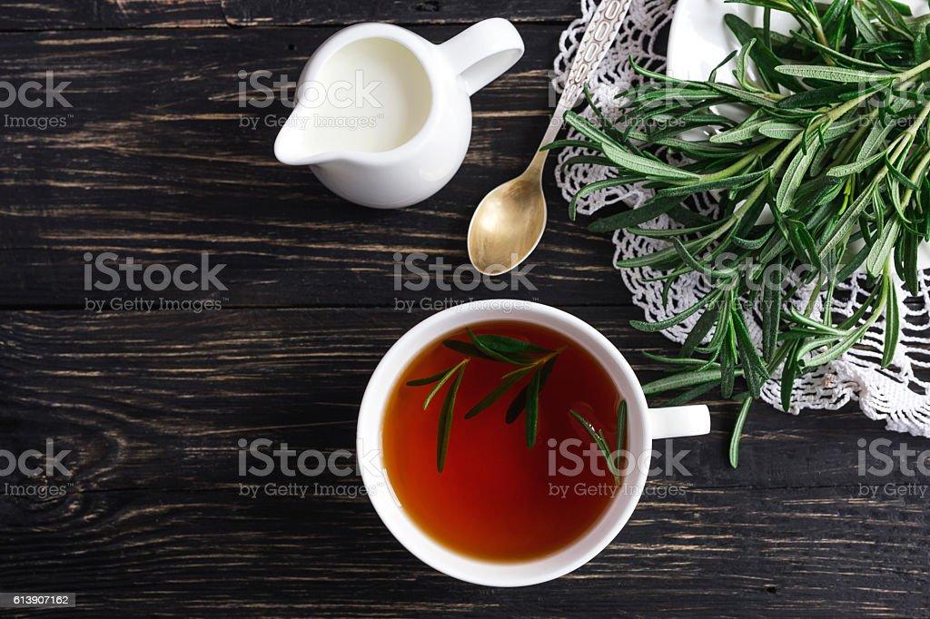 Rosemary tea and milk jar on wooden table. – Foto