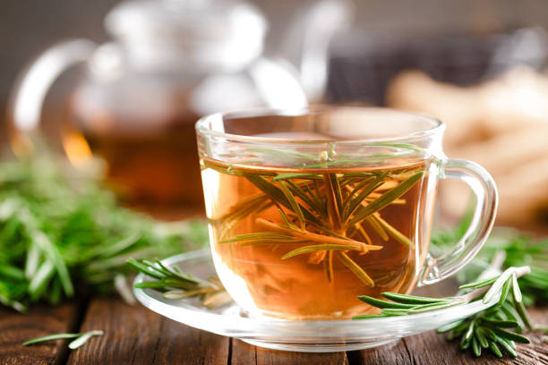 Rosemary tea in glass tea cup on rustic wooden table closeup. Herbal vitamin tea. stock photo