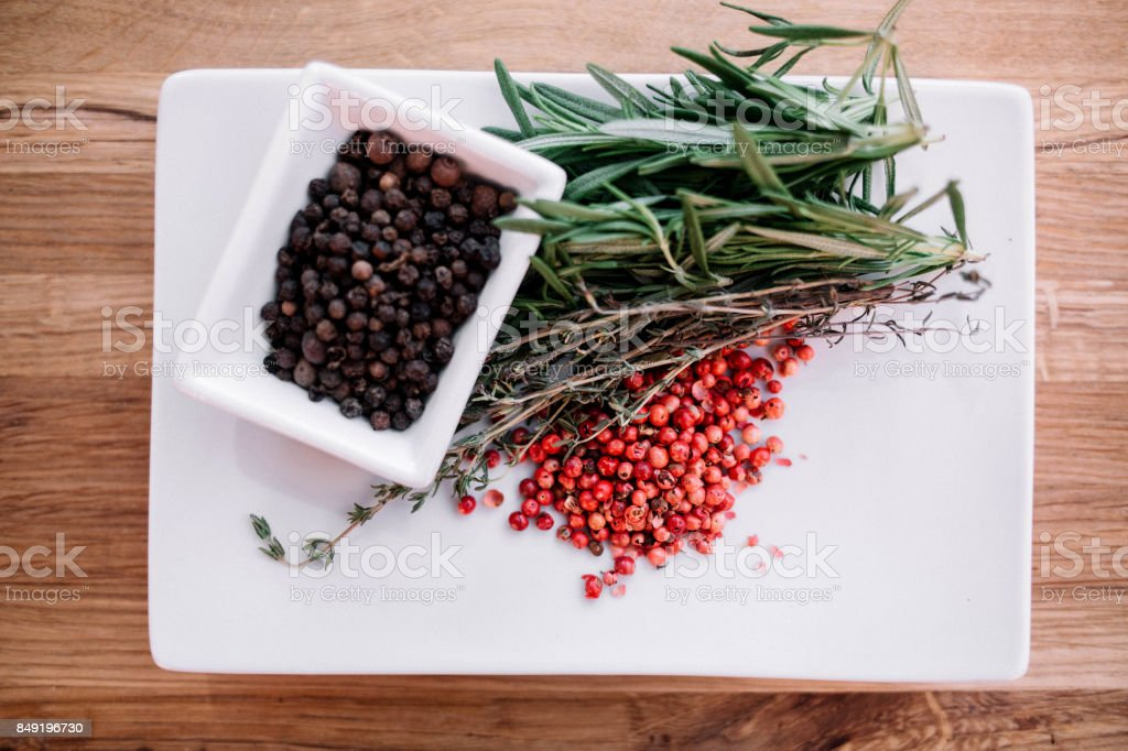 Rosemary with black and pink pepper corns on a white plate on wood background. Top view stock photo